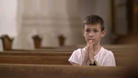 Ernstige jongen die in de alleen Kerk bidden royalty-vrije stock afbeelding