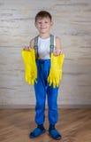 Ernstige jongen die in pantoffels op handschoenen zetten Royalty-vrije Stock Foto