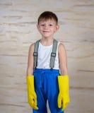 Ernstige jongen die in pantoffels op handschoenen zetten Royalty-vrije Stock Afbeelding