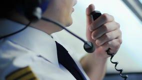 Ernstige kapitein die van lijnvliegtuig informatie door radio, baanplichten doorgeven stock videobeelden