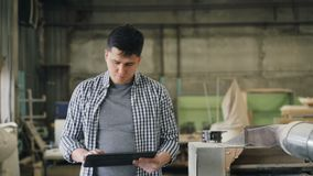 Ernstige kerel die met tablet in houten workshop werken die in ruimte lopen die rond eruit zien stock videobeelden
