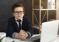 Ernstige kleine jongenszitting bij bureaulijst royalty-vrije stock foto's
