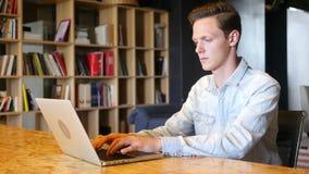 Ernstige knappe mens in overhemdszitting op werkplaats en het werken met computer stock footage