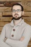 Ernstige manier jonge mens in oogglazen met baard op houten achtergrond Royalty-vrije Stock Fotografie