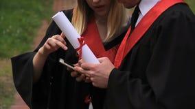 Ernstige mannelijke en vrouwelijke studenten die in academische kleding nieuws op smartphone lezen stock videobeelden