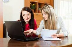 Ernstige meisjes met documenten en laptop Stock Afbeeldingen