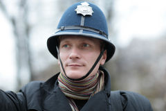 Ernstige mens in Britse politiehoed Stock Afbeelding