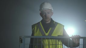 Ernstige mens in de eenvormige bouwers en helm die zich voor de zwarte achtergrond met schijnwerper bevinden Portret van stock video