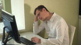 Ernstige mens in de glazenwerken bij de computer stock videobeelden