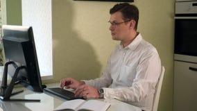 Ernstige mens in de glazenwerken bij de computer stock video