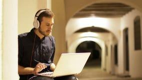 Ernstige mens die laptop met hoofdtelefoons in de nacht met behulp van
