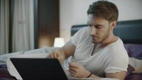 Ernstige mens die met documenten en laptop aan bank bij nacht werken stock video