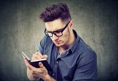 Ernstige mens die nota's met concentratie nemen royalty-vrije stock afbeelding