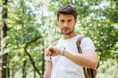 Ernstige mens met rugzak die tijd controleren en horloge bekijken stock afbeelding