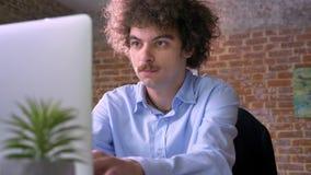 Ernstige nerdy zakenman met het krullende haar typen op laptop en het zitten in modern bureau, programmeursconcept stock videobeelden