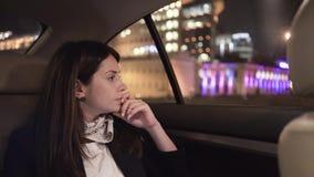 Ernstige onderneemster die een nachtstad bekijken van de achterbank van haar auto stock videobeelden