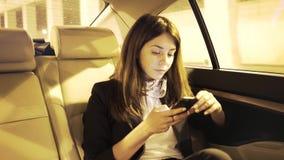 Ernstige onderneemster die haar smartphone in een auto en het denken bekijken stock videobeelden