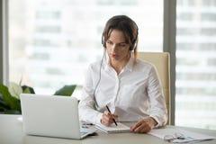 Ernstige onderneemster in hoofdtelefoons letten op webinar op laptop m royalty-vrije stock foto's