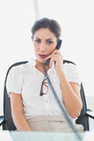 Ernstige onderneemsterzitting bij haar bureau op de telefoon Stock Foto