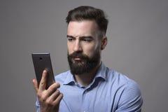 Ernstige ontevreden jonge gebaarde mens holding en het letten op smartphone stock foto