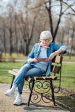 Ernstige oude vrouw die een tijdschrift lezen royalty-vrije stock afbeelding