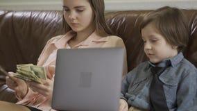 Ernstige oudere zuster en jonger weinig broerzitting op de leerbank Laptop van de jongensholding, meisje het tellen stock footage