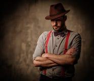 Ernstige ouderwetse mens met hoed die bretels en vlinderdas dragen, die op donkere achtergrond stellen Royalty-vrije Stock Foto