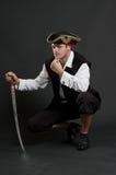 Ernstige piraat met sabelzitting Stock Foto's