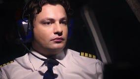 Ernstige professionele proef op het werk, controlerend vluchtindicatoren, die aan bemanning spreken stock videobeelden