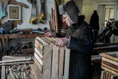 Ernstige rijpe oude grootvader in grijze warme hoed, in oogglazen royalty-vrije stock afbeeldingen
