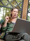 Ernstige Rijpe Vrouw thuis bij Laptop Computer Stock Fotografie