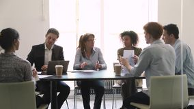 Ernstige rijpe vrouwelijke bedrijfsleider die bij diverse groepsonderhandeling spreken stock footage