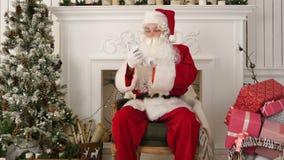 Ernstige Santa Claus die zijn Kerstmispost controleren op de telefoon stock videobeelden