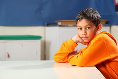 Ernstige schooljongen 10 diepe gedachte in klaslokaal Stock Foto