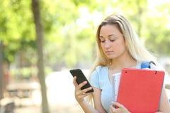 Ernstige student in een park die smartphone met behulp van royalty-vrije stock fotografie