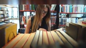 Ernstige studente die een boek in de bibliotheek tussen de planken lezen stock video