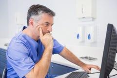 Ernstige tandartszitting en het gebruiken van computer Royalty-vrije Stock Afbeeldingen