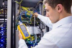 Ernstige technicus die digitale kabelanalysator op server met behulp van stock foto