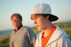 Ernstige tiener met vader stock foto