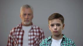 Ernstige tienerjongen die camera, oud mannetje erachter bekijken, verbinding met voorvaderen stock videobeelden