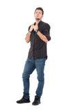 Ernstige toevallige mens die jeans en gecontroleerd grijs overhemd dragen die kraag trekken stock foto's
