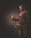 Ernstige Viking met assen in een traditionele strijderskleren, die op een donkere achtergrond stellen Stock Foto