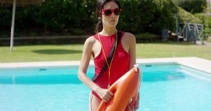 Ernstige vrouw in badmeester eenvormig naast pool stock videobeelden
