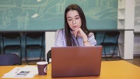 Ernstige vrouw die aan laptop in bureau werken stock videobeelden