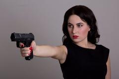 Ernstige vrouw die die met kanon schieten op grijs wordt geïsoleerd Stock Afbeelding