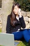 Ernstige vrouw die met telefoontablet en computer werken royalty-vrije stock afbeeldingen