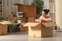 Ernstige vrouw die naar huis unboxing bezittingen in de nacht bewegen royalty-vrije stock afbeelding