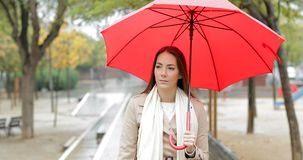 Ernstige vrouw die onder de regen in een park lopen stock videobeelden