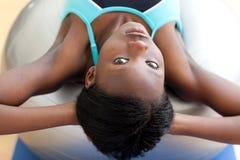 Ernstige vrouw die zitten-UPS met een pilatesbal doet Stock Foto
