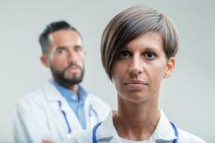 Ernstige vrouwelijke arts of verpleegster in een medisch team stock afbeeldingen